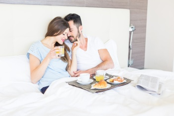 Couple Having Breakfast at Hotel Bedroom